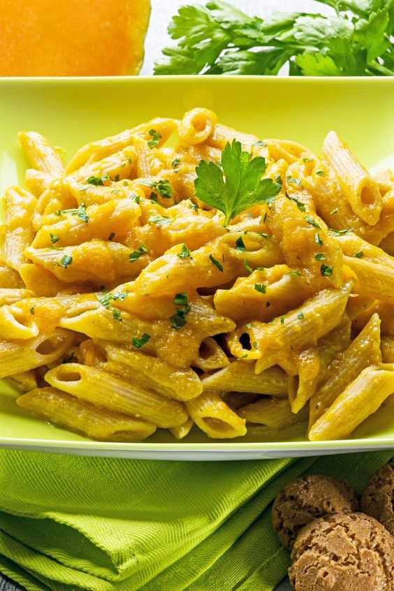 Pumpkin Penne Pasta on a lime green plate on top of a lime green place mat.