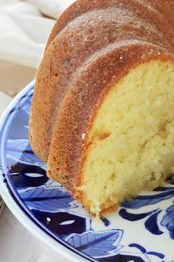 Closeup of a lemon bundt cake with a slice removed. Sitting on a decorative blue and white plate.
