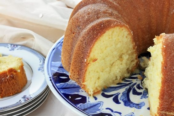A lemon bundt cake with a cut slice on a small plate next to it.