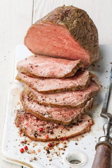 Sliced Roast Beef on a white cutting board.