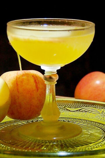 Apple Cider Vodka Martini in a clear glass on a glass plate.