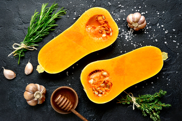 Butternut squash cut in half on a black background surrounded by herbs.