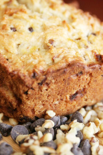 Closeup of zucchini bread surrounded by chocolate chips and chopped walnuts.