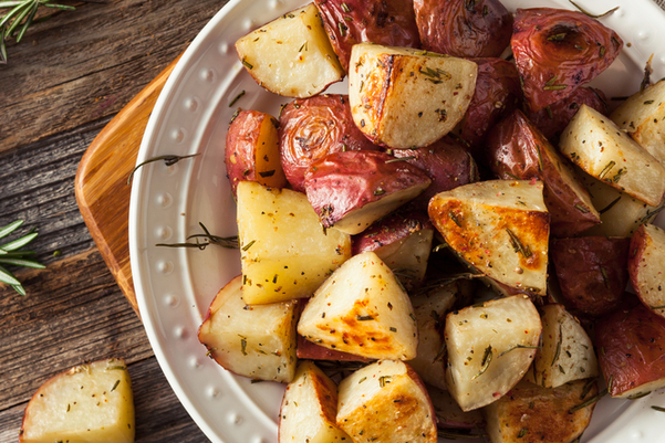 Closeup of Rosemary Roasted Red Potatoes  in a white bowl on a wooden background.